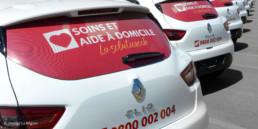 Domaine aide et soins à domicile. Autocollant perforé avec logo de la-solution.ch sur vitre arrière du véhicule professionnel, création graphique bureau région Yverdon-les-bains